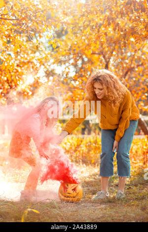 Halloween Preparaton concepto. Madre e hija de pie afuera haciendo gas en colores alegres de calabaza
