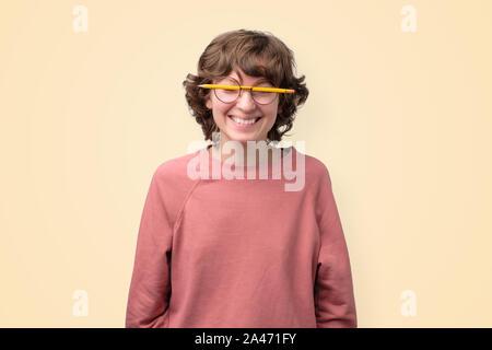Joven mujer divertida en vidrios sin lentes está cansado de estudiar.
