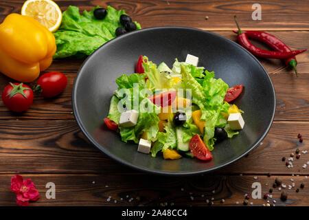 Luz ensalada de verduras. Cerezas frescas, pepinos, pimientos, el romano, el queso Feta, aceitunas, aceite de oliva en una placa negra sobre un fondo de madera