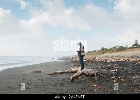 Hombre de pie en driftwood mirando el teléfono móvil en la playa.