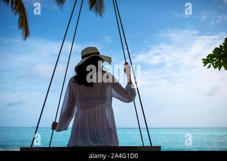 Joven Mujer hermosa relajante en swing colgando de palma de coco en la exótica playa.mar azul y la arena blanca. Chica de moda disfrutar junto al mar. Morena g Foto de stock