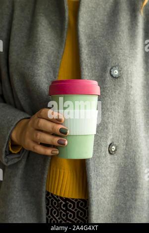Copa Eco de bambú en las manos de una mujer en una capa gris y un suéter otoño amarillo