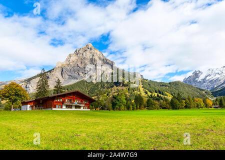 Chalet de madera en Kandersteg village, Cantón de Berna, Suiza, Europa, Otoño de árboles y montañas panorama Foto de stock