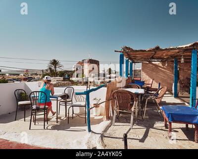 Joven chica rubia se sienta en la terraza del restaurante marroquí rural en día soleado, Marruecos