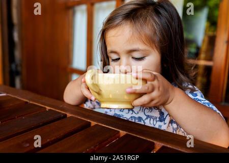 Niña bebiendo una copa de té