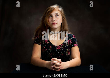 Horizontal de una foto de estudio pre-adolescentes señorita con sus manos entrelazadas, mirando hacia arriba y orando. Fondo marrón con espacio de copia.