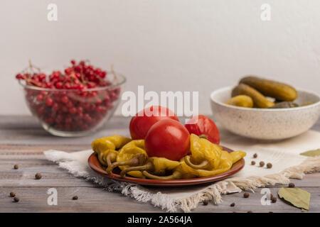 En escabeche pimientos y tomates caseros en una placa de cerámica en una servilleta de lino. Cerca de encurtidos y viburnum en cuencos