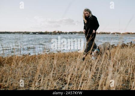 Mujer caminar a su perro en la playa en invierno Foto de stock