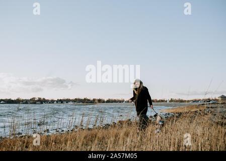 Mujer paseando a un perro en la playa en el invierno Foto de stock