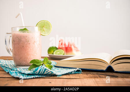 Una plana cuadrada (laicos ración) Foto con mesa de desayuno batido de sandía, libro de teléfono y rodajas de frutas en la placa -alimentos y dietas concepto imagen.