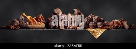 Trufas de chocolate con trozos de chocolate. Chocolate con ingredientes y especias sobre un fondo oscuro. Copie el espacio.