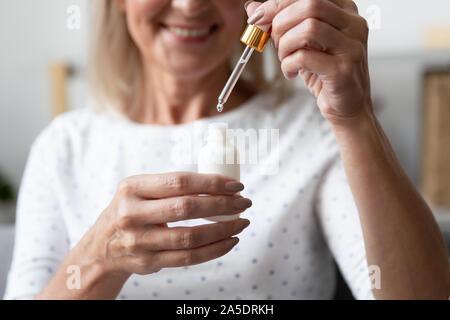 Mujer madura feliz celebración cara suero para el cuidado de la piel, cerrar