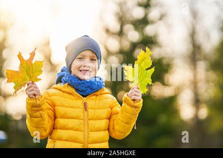 Niño feliz muchacho jugando fuera en otoño