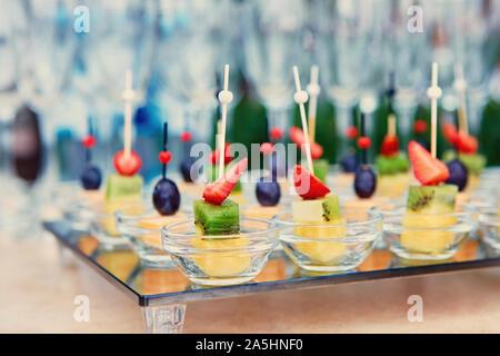 Canapés de fruta en un cajón de vidrio, en el fondo de copas de vino y champagne. Concepto de catering. Foto de stock