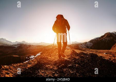 Silueta de caminante con mochila y caminar polacos va en montañas y el atardecer