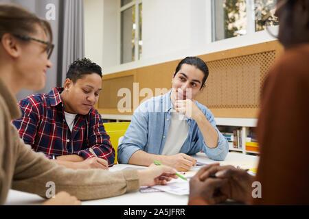 Grupo multiétnico de los estudiantes del grupo de discusión y las lluvias de ideas de proyecto mientras está sentado en una mesa en la biblioteca de la universidad, espacio de copia