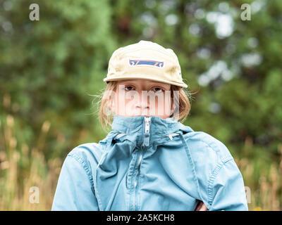 Retrato de adolescente con paravientos y sombrero al aire libre
