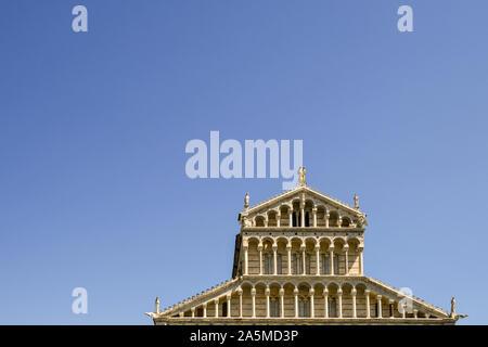 Parte superior exterior de la fachada de la Catedral de Pisa (Duomo di Santa Maria Assunta) en la famosa Piazza dei Miracoli contra el cielo azul claro, Toscana, Italia