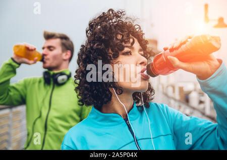 Hombre y mujer beber bebida energética de la botella después de fitness sport ejercicio