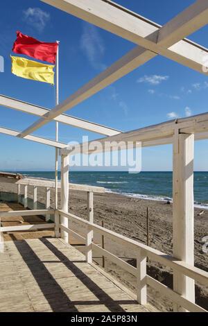 Playa banderas de advertencia de seguridad en un día ventoso en una playa en el sur de toscana