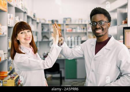 Dos farmacéuticos colleages feliz, hombre y mujer caucásica africanos trabajan en farmacia, sonriente, dando cinco y divertirse.