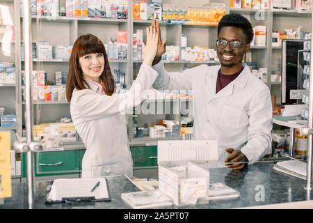 Dos gracioso feliz colleages farmacéuticos, hombre africano y mujer caucásica trabajando en farmacia, sonriente, dando cinco y divertirse.