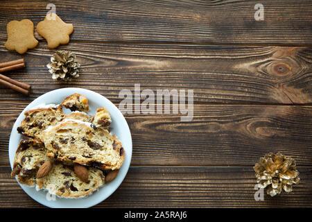 Pastel de Navidad y gingerbread cookies en tabla de madera marrón. Conos de oro y canela decoraciones. Espacio libre para el texto. Espacio para un saludo
