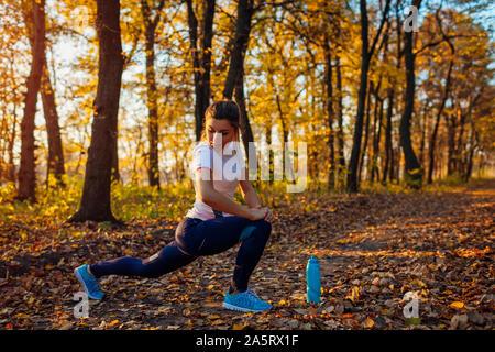 Formación y ejercicio en otoño del parque. Mujer joven estirar las piernas al aire libre. Activo estilo de vida saludable. Entrenamiento
