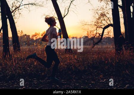 Runner formación en otoño de parque. Mujer corriendo con la botella de agua al atardecer. Un estilo de vida activo. Silueta de slim joven
