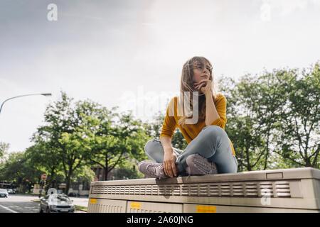 Mujer joven sentado en una caja en la ciudad