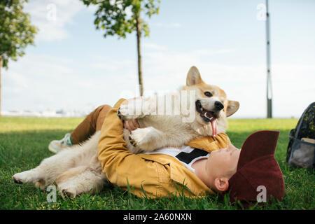 Chico con Welsh Corgi Pembroke en un parque