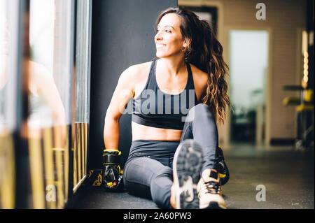 Boxer hembra sonriente descansa después del entrenamiento de boxeo