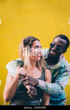 Retrato de pareja feliz delante de pared amarilla Foto de stock
