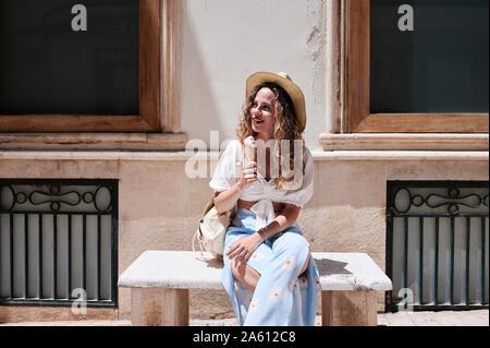 Mujer joven sentada en la banca de piedra comer helado Foto de stock