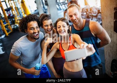 Grupo de gente deportiva en un gimnasio teniendo selfie. Conceptos acerca de su estilo de vida y deportes en el club de fitness