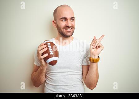 Joven sosteniendo el rugby fútbol americano bola sobre fondo aislado muy feliz apuntando con la mano y de los dedos al lado