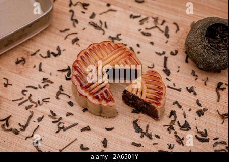 Preparación al concepto del festival chino de mediados de otoño. Comida tradicional para las vacaciones deliciosa tarta de luna en la bandeja de madera con té pu'er negro.