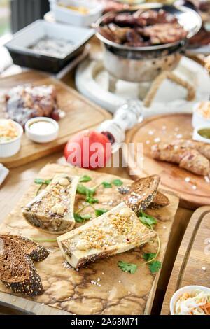 Médula ósea de carne con salsa chimichurri y tostada bun. El menú del restaurante barbacoa. Muchos de los diferentes grupos de alimentos en la mesa. Cena fiesta o banquete