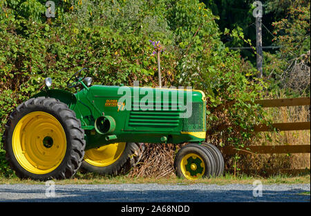 Una vista lateral de una antigua granja Oliver tractor estacionado para que la gente pueda ver a lo largo de una carretera en British Columbia, Canadá.