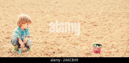Niño divirtiéndose con poca pala y planta en maceta. La siembra en el campo. Pequeño Ayudante en el jardín. Plantar flores en campo chico cavar el suelo. Concepto de la madre naturaleza. Trabajar en la granja. La siembra de las plántulas.