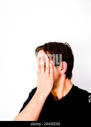 El hombre que cubren la cara con la mano en la vergüenza - vista lateral