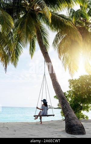 Joven Mujer hermosa relajante en swing colgando de palma de coco en la exótica playa. Mar azul y la arena blanca. Chica de moda disfrutar junto al mar. Retrato Foto de stock