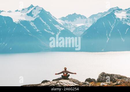 El padre con el bebé meditando en las montañas de yoga al aire libre relajado estilo de vida familiar saludable vacaciones viajes la armonía con la naturaleza, concepto