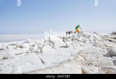 Hombre adulto joven al aire libre con su perro divirtiéndose en paisaje de invierno Foto de stock