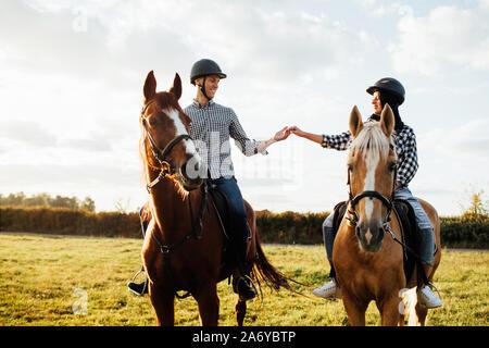 Feliz pareja amorosa pasando tiempo con caballos en el rancho
