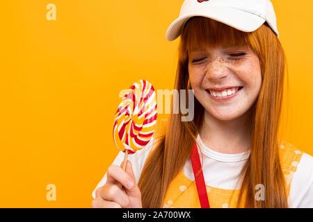 Colegiala pelirroja sobre un fondo naranja con un lollipop en sus manos entornar con una sonrisa en su cara, retrato emocional