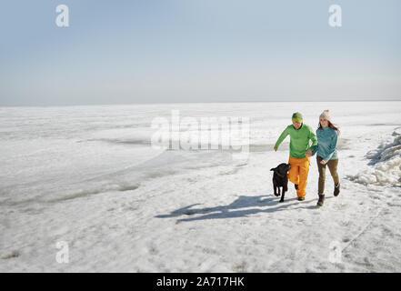 Adulto joven pareja afuera con perro divirtiéndose en paisaje de invierno Foto de stock