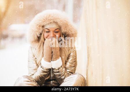 Preciosa niña alegre caucásica vistiendo mono dorado posando sentado sobre la nieve, sosteniendo sus palmas juntas como si en la oración, sonriendo, soñando, disfrutando de TIM