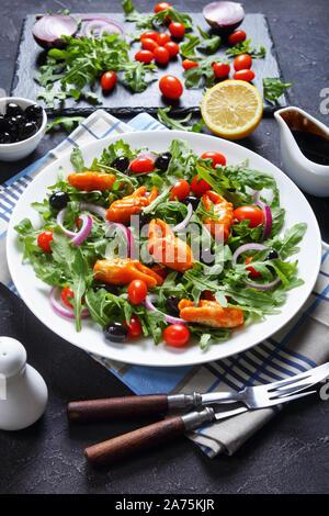 Cierre de pinzas de cangrejo ensalada de rúcula con aceitunas negras, tomates cherry y cebolla roja servida en una placa blanca, sobre una tabla concreta con los ingredientes,