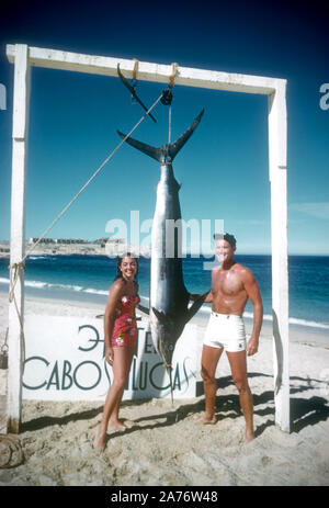 BAJA CALIFORNIA, MÉXICO - JUNIO DE 1962: el actor y ex jugador de béisbol Chuck Connors (1921-1992) y la actriz prometido Kamala Devi (1934-2010), posan para una fotografía delante de un marlin que Connors capturado mientras estaba en un viaje de pesca alrededor de junio de 1962, en Baja California, México. (Foto por Hy Peskin) (número de registro: X8569)